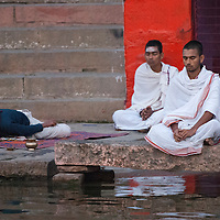 Morning rituals being performed on the banks of the holy Ganges River in Varanasi, India at sunrise.