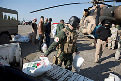 © Licensed to London News Pictures. 11/12/2014. Fishkhabour, Iraq. Members of the Iraqi-Kurdish security forces load up an Iraqi Air Force Mi-17 Hip helicopter with supplies for Yazidi refugees on Mount Sinjar.<br /> <br /> Although a well publicised exodus of Yazidi refugees took place from Mount Sinjar in August 2014 many still remain on top of the 75 km long ridge-line, with estimates varying from 2000-8000 people, after a corridor kept open by Syrian-Kurdish YPG fighters collapsed during an Islamic State offensive. The mountain is now surrounded on all sides with winter closing in, the only chance of escape or supply being by Iraqi Air Force helicopters. Photo credit: Matt Cetti-Roberts/LNP
