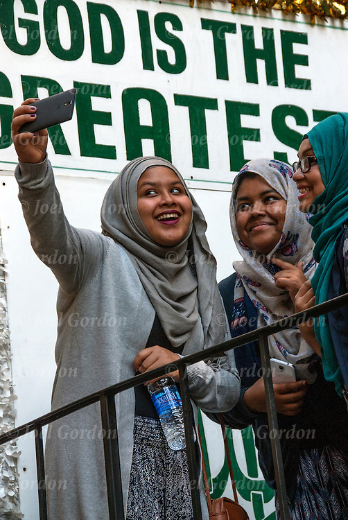 American Muslim teenage girls taking selfie at the United Muslim Day Parade in NYC.<br /> <br /> A selfie is a self-portrait photograph featuring the photographer, typically taken with either a <br /> hand-held digital camera or camera phone. Selfies are often shared on social networking <br /> services such as Facebook, Instagram , Snap Chat and Twitter. They are usually flattering and <br /> made to appear casual.<br /> <br /> Most selfies are taken with a camera held at arm's length or pointed at a mirror, rather than <br /> by using a self-timer.