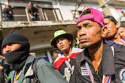 17 JANUARY 2014 - BANGKOK, THAILAND: Security guards for anti-government protestors look for unknown assailants who threw an IED at an anti-government protest march. The attackers were not found but officials claim to have found a weapons cache in an abandoned building nearby. Friday was day 5 of the anti-government Shutdown Bangkok protests. The protest, led by the People's Democratic Reform Committee, is calling for the suspension of elections pending political reform in Thailand. There was violence at several sites in Bangkok Friday, including running battles between government opponents and supporters at one site and an IED attack by unknown assailants on anti-government protestors at another site.    PHOTO BY JACK KURTZ