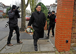 © Licensed to London News Pictures. 19/12/2011, London, UK. A man carrying flowers arrives at the rear entrance to the North Korean embassy in West London. Kim Jong Il's death on Saturday, aged 69, was announced last night in a special broadcast by state TV from the North Korean capital. Photo credit: Stephen Simpson/LNP