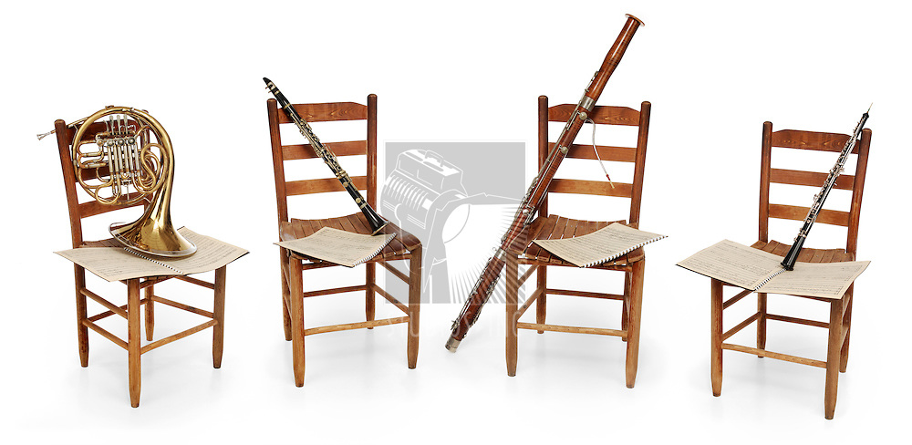 French horn, clarinete, bassoon and oboe sitting on empty chairs with sheet music on white background