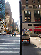 The view is cut in half by a pole, giving the impression of two seperate scenes.  A pedicab is in the foreground in the right side of the frame and a row of buildings in the left side.