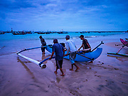 03 AUGUST 2017 - KUTA, BALI, INDONESIA:  Villagers push their outrigger canoes into the surf before sunrise along Jimbrana Beach in Kuta. The beach is close to the airport and a short drive from other beaches in southeast Bali. Jimbrana was originally a fishing village with a busy local market. About 25 years ago, developers started building restaurants and hotels along the beach and land prices are rising. The new emphasis on tourism is changing the nature of the area but the fishermen are still busy very early in the morning.    PHOTO BY JACK KURTZ