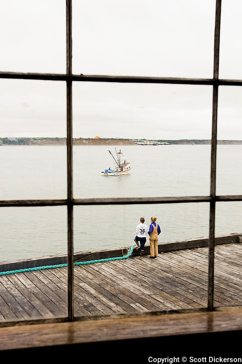 Deckhands look out from the Trident Seafoods cannery dock towards a commercial fishing boat on the Naknek River, South Naknek, Bristol Bay, Alaska. As viewed through an old cannery window.