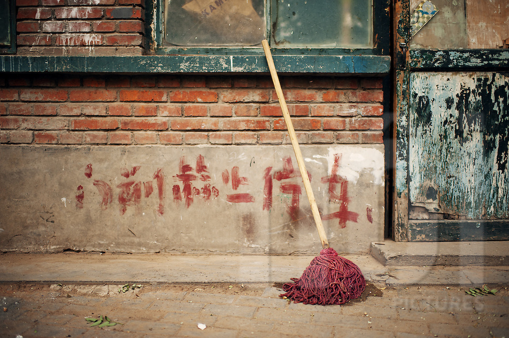 Still life scenes from the old streets of Beijing, China. Broom against a wall