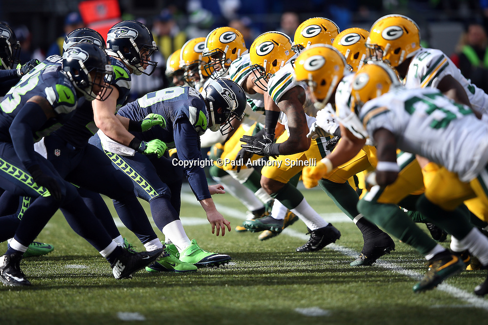 The Seattle Seahawks offensive line snaps the ball at the line of scrimmage as the Green Bay Packers defensive line rush during the NFL week 20 NFC Championship football game against the Green Bay Packers on Sunday, Jan. 18, 2015 in Seattle. The Seahawks won the game 28-22 in overtime. ©Paul Anthony Spinelli