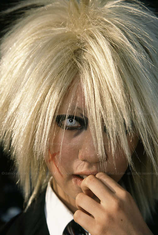 A young cosplayer girl with spiky blond hair and heavy eye make up and coloured contact lenses. Harajuku, Tokyo, Japan September 2005
