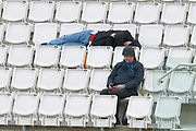 A spectator in the stands spread across a row of seats catching up with some sleep during the first day of the Specsavers County Champ Div 1 match between Hampshire County Cricket Club and Essex County Cricket Club at the Ageas Bowl, Southampton, United Kingdom on 5 April 2019.