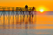People enjoying a sunrise on a 'stick' pier over Lake Winnipeg<br /> Matlock<br /> Manitoba<br /> Canada