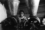 Young girl processing her family's daily bowl of fresh maize kernels in order to make tortillas. <br /> Community of Nueva Esperanza, El Salvador, 1999.
