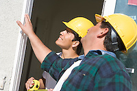 Construction Workers examining window frame
