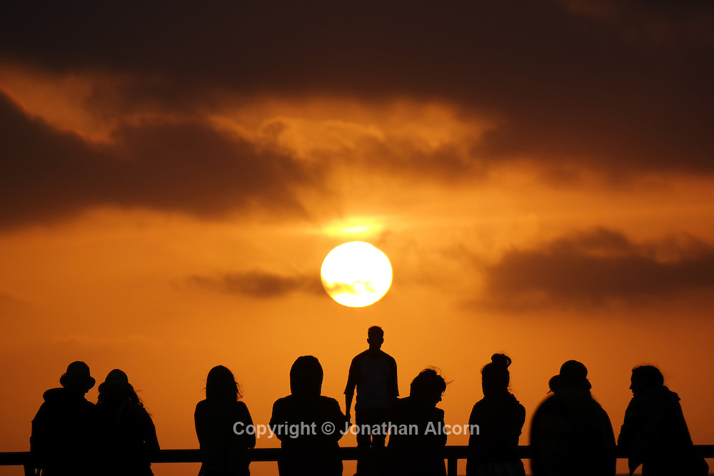 People gather at the Venice Skate Park in Venice Beach as the sun begins to set