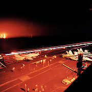The glow and trails of night manoeuvres seen from an upper deck of the US Navy's Harry S Truman aircraft carrier whilst on exercise somewhere in the Persian Gulf. <br /> The Truman is the largest and newest of the US Navy's fleet of new generation carriers, a 97,000 ton floating city with a crew of  5,137, 650 are women. The Iraqi no-fly zones (NFZs) were proclaimed by the United States, United Kingdom and France after the Gulf War of 1991 to protect humanitarian operations in northern Iraq and Shiite Muslims in the south. Iraqi aircraft were forbidden from flying inside the zones. The policy was enforced by US, UK and French aircraft patrols until France withdrew in 1998.
