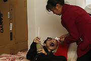 CHONGQING, CHINA - MAY 09: (CHINA OUT) <br /> <br /> Cancer Makes 15-year-old Boy Suffer Face Swell<br /> <br /> Nie Song's mother feeds her cancer-tortured son liquid diet in Chongqing, China. A 15-year-old boy Nie Song suffering from cancer can only take in liquid diets and stay in bed because it has made his face swelled out of shape. The boy who has initial sore gum was diagnosed with tumor but his parents neglected to take precautions, which has led to a malignant tumor that makes his mouth unable to close. <br /> ©Exclusivepix