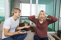 Man trying to talk as woman yells out aloud in living room at home