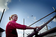 UNITED KINGDOM, Basildon : A young resident sits on barricades next to the main gate at Dale Farm travellers camp on September 19, 2011 in Basildon, England.  © Christian Minelli.