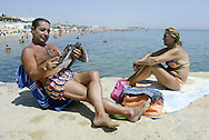 Portuguese summer. A man reads a magazine and sunbathes in Carcavelos beach outskirts of Lisbon.