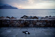 A cat lies at The Lybian Sea Coast in Palaiochora during the low season, normally hundreds of tourists are walking the shore during the high season. Palaiochora is a small town in the Chania regional unit on the island of Crete, Greece. It is located 77 km south of Chania, on the southwest coast of Crete and occupies a small peninsula 400m wide and 700m long. The town is set along 11 km of coastline bordering the Libyan Sea. Its population was 1,675 in the 2011 census. Palaiochora's economy is based on tourism and agriculture (mainly tomatoes cultivated in glass houses and also olive oil).
