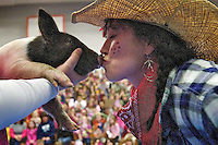 Lisa Pica, principal of Hayden Meadows Elementary, kisses a two-week-old pig during an assembly Friday at the school.The gathering was held to celebrate the student body's fund raising effort which raised $17,550 through the school's spring raffle event.  .