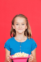 Portrait of young girl holding popcorn container against red background