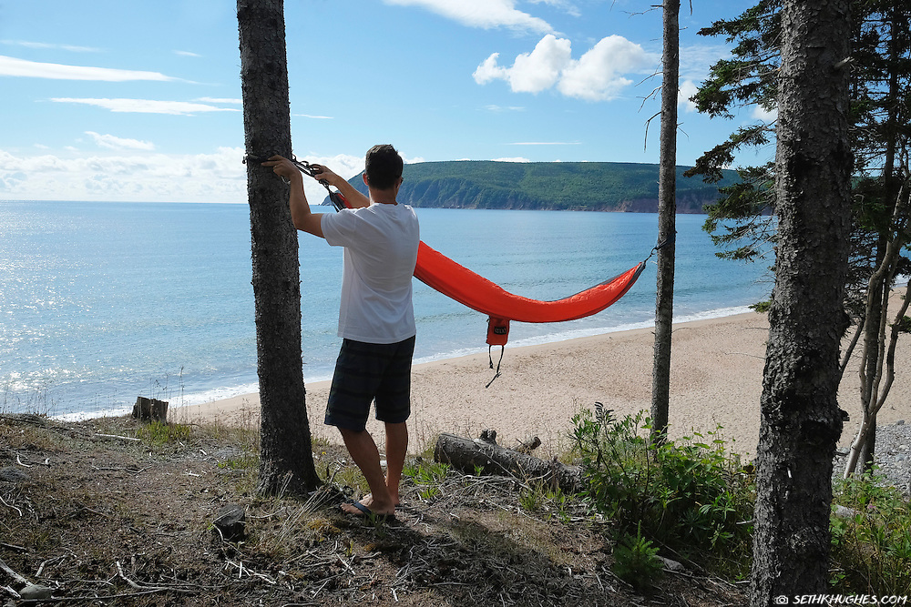 A man sets up a hammock overlooking Ingonish Beach, Cape Breton Highlands National Park, Nova Scotia, Canada.