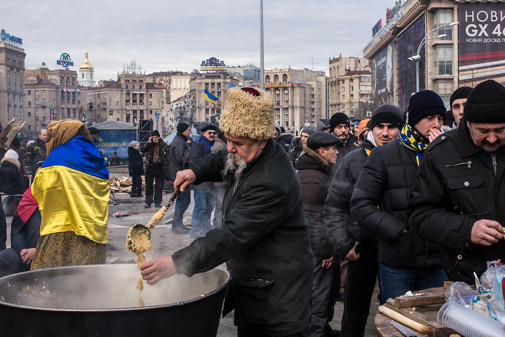 KIEV, UKRAINE - DECEMBER 4: A man serves soup to anti-government protesters in Independence Square on December 4, 2013 in Kiev, Ukraine. Thousands of people have been protesting against the government since a decision by Ukrainian president Viktor Yanukovych to suspend a trade and partnership agreement with the European Union in favor of incentives from Russia. (Photo by Brendan Hoffman/Getty Images) *** Local Caption ***