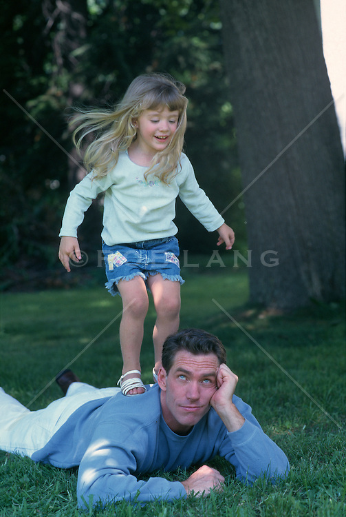 Girl Jumping On A Man's Back Outdoors