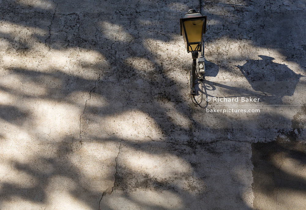 Shadow patterns and a street lamp on a wall on 25th May, 2017, in Lagrasse, Languedoc-Rousillon, south of France. Lagrasse is listed as one of France's most beautiful villages and lies on the famous Route 20 wine route in the Basses-Corbieres region dating to the 13th century.