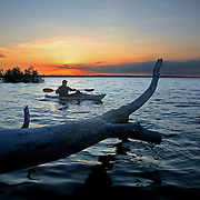 Ron Huelse skims  along the southern shore of Lake Red Rock in his kayak as sunrise reveals another crystal clear day on Iowa's largest lake.  Also with him is his dog Louis.<br /> <br /> Huelse's daybreak ritual is often a photographic mission, as he records the habitats that the lake has fostered.  photo by david peterson