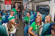 MARCH 17, 2011 - LONG ISLAND NY: Dressed for St. Patrick's Day in green, young adults riding Long Island Railroad LIRR to Penn Station to celebrate in Manhattan, NY, USA, morining of St. Patrick's Day. The LIRR added more than a dozen trains to Manhattan for St. Patrick's Day Parade. At rear, ads for (left) ING Direct and (right) New York Lottery. Train at Jamaica Station stop.  EDITORIAL USE ONLY)