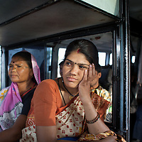 "Vandana Dube (foreground), the manager of Dharkan 107.8 travels on a local bus with her program-maker colleague Ramvati Adivasi. Before the official launch of the community radio station in July 2009, Dube and her colleagues have recorded several programs informing women of government health services. They then travel to villages to play these programs to a local audience. Dube calls the airing of these pilot shows ""narrowcast"" in anticipation of the imminent ""broadcast"". As well as her role at Dharkan 107.8, Adivasi is is an ASHA (local female health advisor). She provides a free referral service to local women, keeping them in touch with government health services. Adivasi receives a fee from the government for every referral. This is one means by which the government and partners UNICEF are increasing the rate of institutional deliveries in Madhya Pradesh. ..Shivpuri district in Madhya Pradesh suffers from poor health outcomes. Of particular concern is the high rate of maternal mortality. One of the Indian government's aims, with partners Unicef, is to encourage the population to adopt practices to improve sanitation and health practices. In an area made up of traditionally disadvantage groups and suffering low literacy rates, this can be a challenge. ..A survey found that radio was the most readily accessible media by the Shivpuri community with more than half saying they tuned in several times a day. ..Dharkan 107.8 FM will go on air in July. The station that will broadcast to 75 villages in a 15-kilometer radius reaching 170,000 people...Rather than preaching educational messages, the station, which is already producing pilot programs, uses humor and folk artists performing in the local language to entertain and inform their audiences. There is a major impact, especially on women, who are contributing their voices to such wide-ranging issues as caste discrimination, female feticide and women's empowerment. ..Photo: Tom Pietrasik.Shivpuri, Madhya Pradeh. India."