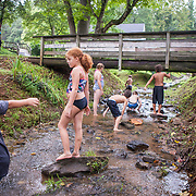 Olivia Johns, stands on a rock as other children play in the Falling Rock Creek, looking for crayfish and other animals on Friday, August 5, 2016.  On the last day of a week long Bible study camp at the Monacan Tribal Center, the children took time out to play outside.  Olivia's mother and grandmother grew up playing in the creek that runs past the church, old schoolhouse and tribal center.  John Boal Photography
