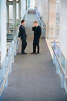 Businessmen in office building hallway