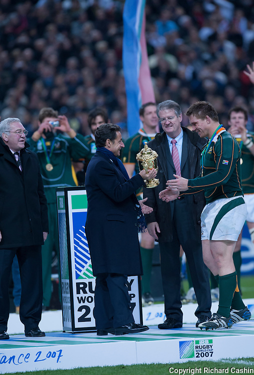 President of France Nicolas Sarkozy presents Webb Ellis Cup to South African rugby Captain John Smit after the 2007 Rugby World Cup Final at Stade de France in Paris, France