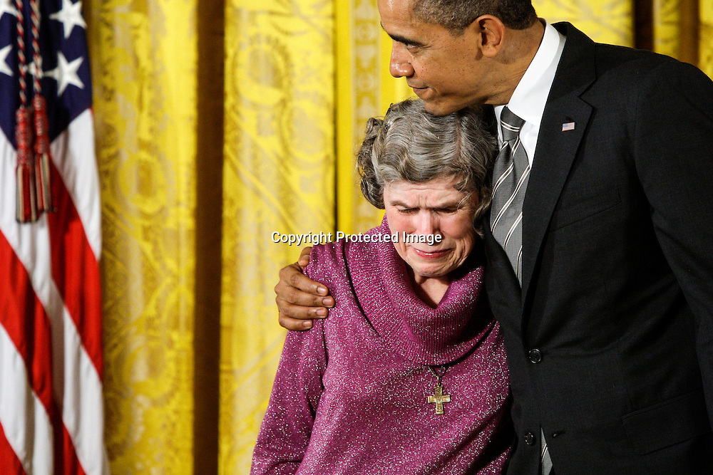 U.S. President Barack Obama hugs Mary Jo Copeland of Minneapolis as she cries upon receiving the Presidential Citizens Medal for the Sharing and Caring Hands social assistance safety net she founded in 1985, in the East Room at the White House in Washington, February 15, 2013.