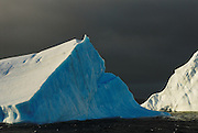 Side light trianglar icebergs under a moody clouds.