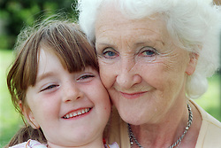 Portrait of grandmother and granddaughter smiling,
