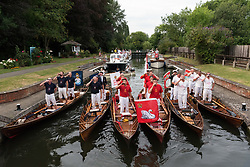 Swan Upping crew make a toast to Queen Elizabeth II at Old Windsor Lock on the River Thames near Windsor, Berkshire. The annual event dates from medieval times, when The Crown claimed ownership of all mute swans which were considered an important food source for banquets and feasts. Today, the cygnets are weighed and measured to obtain estimates of growth rates and the birds are examined for any sign of injury, commonly caused by fishing hook and line. The cygnets are ringed with individual identification numbers by The Queen's Swan Warden, whose role is scientific and non-ceremonial. The Queen's Swan Marker produces an annual report after Swan Upping detailing the number of swans, broods and cygnets counted during the week. . Photo credit: Ray Tang/LNP