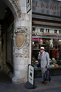 A foreign-looking gentleman stands talking into his phone's hands-free outside Laird Hatters, on 5th July 2017, on the Strand in central London, England.