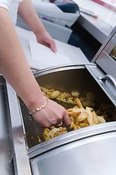 Bulgarian woman serving chips out of deep fat fryer,