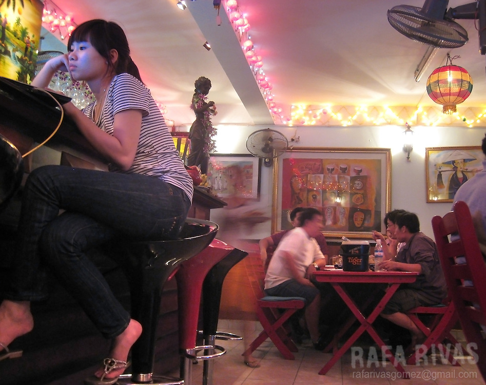 A girl looks at her laptop while customers have dinner at a restaurant in Saigon, Vietnam, on January 2009.