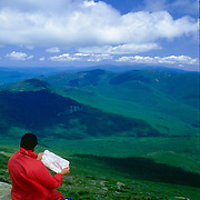 A hiker reads a map from the summit of Mt. Lafayette, the highest point in the Franconia Range, overlooking the Pemigiwasett Wilderness in the White Mountain National Forest