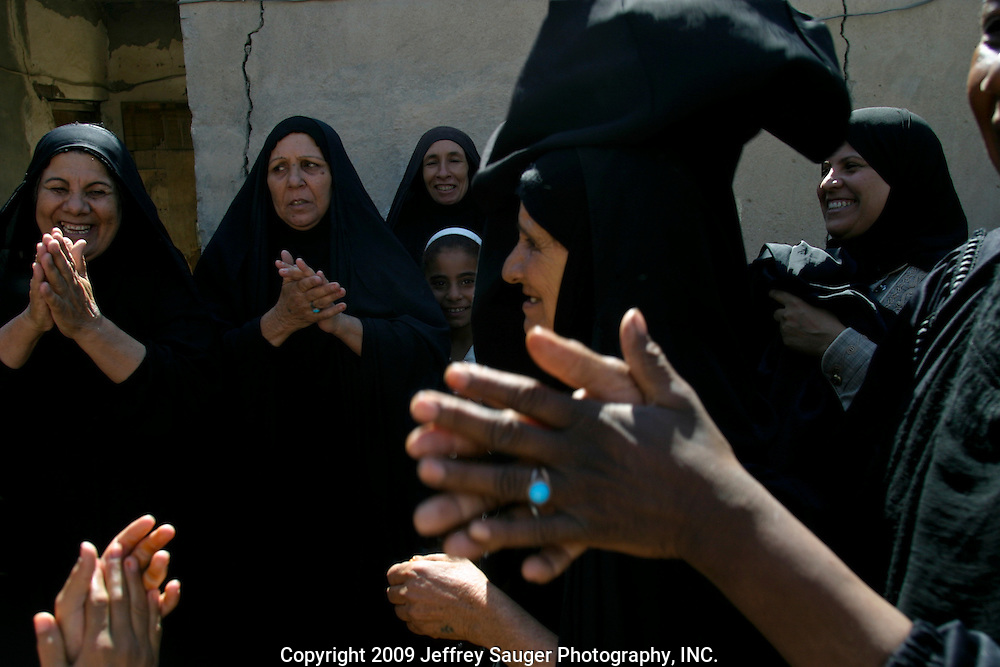 The Al-Kasid women celebrate during the family's homecoming in the village Suq ash Shuyukh on the outskirts of Nasiriyah, Iraq, July 30, 2003. The celebration lasts three days with different tribal chiefs, family members and friends coming and going. The women wear black as a sign of mourning for a close loved one that has died; some for a year and some forever after the death...The Al-Kasid family fled Iraq after the Gulf War and their part in the uprising against Saddam Hussein in 1991, spent 3 years in Rafa, Saudi Arabia and finally settled in Dearborn, MI. The family hasn't been home to Iraq in 13 years.