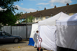 © Licensed to London News Pictures. 16/05/2017. London, UK. Police forensics enter a tent at the scene where a search continues for the body of murdered schoolgirl Danielle Jones at a block of garages in Stifford Clays in Thurrock, Essex. The 15-year-old was last seen on Monday June 18 2001 at about 8am when she left her home in East Tilbury to catch the bus to school.  Photo credit: Ben Cawthra/LNP