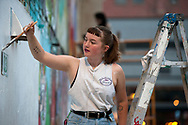 Ashley Dreyfus paints the undercoating for her mural during the Freak Alley Gallery seventh annual mural event on August 5, 2017 in downtown Boise, Idaho. <br /> <br /> Freak Alley Gallery's week long event provided an &quot;art-in-motion&quot; experience as it welcomed the public to watch artists work on their murals.