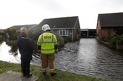© Licensed to London News Pictures. 06/01/2014, Christchurch, UK. A firefighter talks to the residents outside their flooded houses at Burton, Christchurch, England , Monday, Jan. 6, 2014. Part of UK continue to be affected by floods and strong wind. Photo credit : Sang Tan/LNP