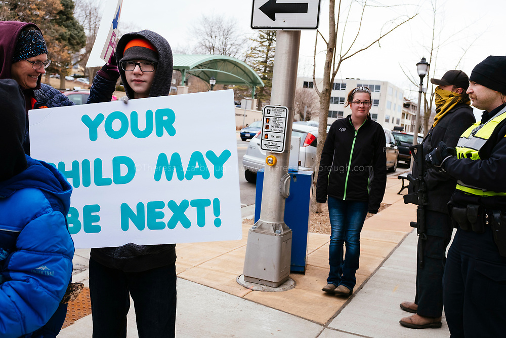 Janesville, Wisconsin, USA. 24th March, 2018. Protesters march to Congressman Paul Ryan's, Speaker of the House, office building in Janesville, Wisconsin's March for Our Lives event. In the background (right) counter protesters stood silently, one man dressed in all black with an assault rifle.