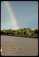 Men in a canoe loaded with boxes drift on Jurua River as rainbow looms in distance; Eirunepe, AM. Brazil
