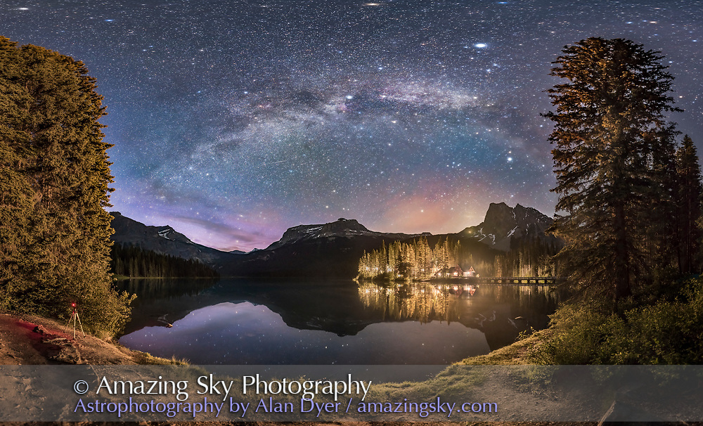 The Milky Way arching over Emerald Lake and Emerald Lake Lodge in Yoho National Park, BC. This was on June 6, 2016 and despite it being about 1:30 am, the sky, especially to the north at left, is still lit by blue twilight from the short solstice night. <br /> <br /> Unfortunately, the lights from the Lodge, in particular one bright unshielded sodium vapour light, illuminates the foreground and even across the lake. The lights are themselves not overly bright but the long exposures in such images really brings out how much they do light the night landscape. They should be shielded or reduced in number, or put on motion sensors to light only when necessary. Or all of the above! <br /> <br /> The Summer Triangle stars are at centre top. High haze fuzzes the star images. Vega is the brightest star at upper right. <br /> <br /> Mt. Burgess, home to the famous Burgess Shale Cambrian explosion fossils, is at centre. <br /> <br /> My other camera is at left, on a tripod, shooting a time-lapse sequence. I could have cloned it out but decided to leave it in. <br /> <br /> This is a panorama over about 180&deg;, made of 24 segments but cropped in quite a bit from the original, and all shot on the iPano panning unit. Each exposure was 30 seconds at f/2.2 with the Sigma 24mm lens and Nikon D750 at ISO 4000. One short exposure of the lodge was blended in to reduce its light glare. Stitched in PTGui. The original is 15,000 x 9,000 pixels.